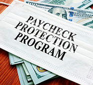 White Facemask Over Dollar Bills With the Words Paycheck Protection Program